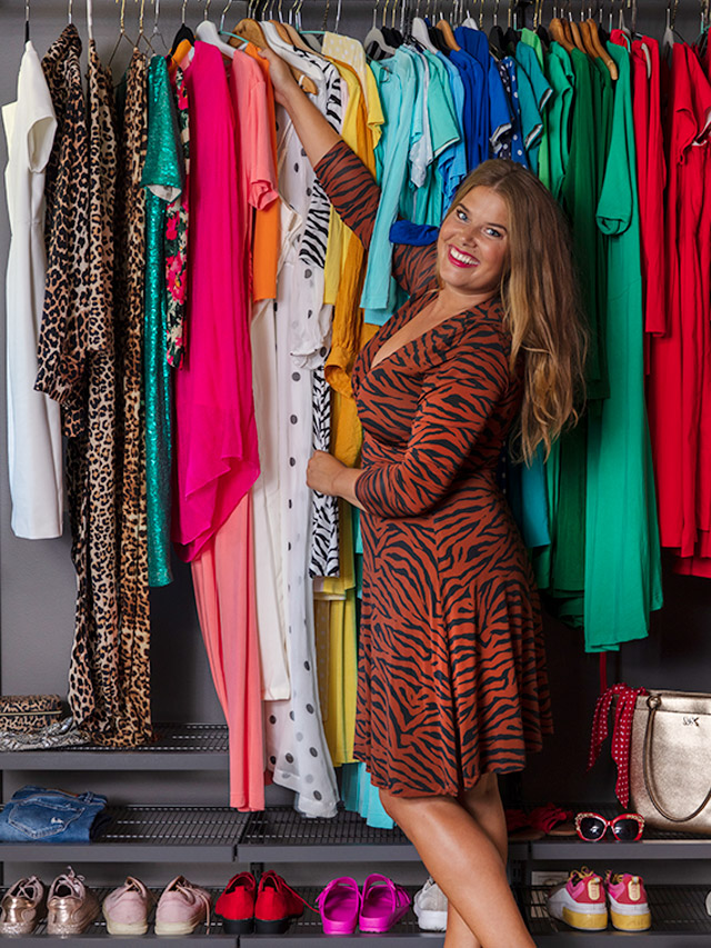 Jessica in front of her colourful wardrobe