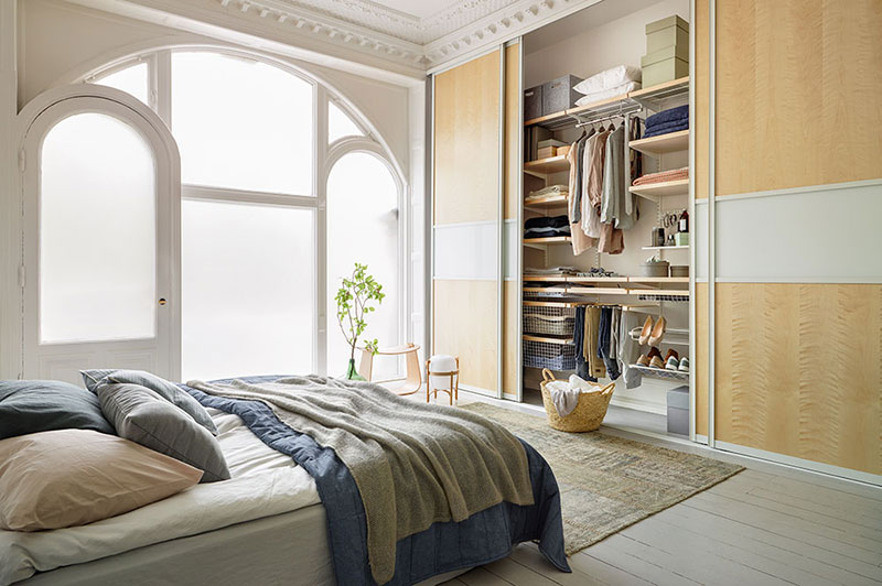 Wardrobe with sliding doors in a bedroom with magnificent windows. Sliding doors create space in the bedroom   Elfa Inspiration