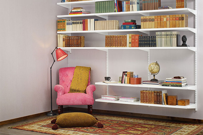 A cosy reading corner with armchair and wall-mounted bookshelves